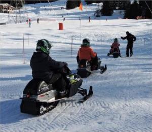 Les enfants évoluent sur les motoneiges dans un espace sécurisé